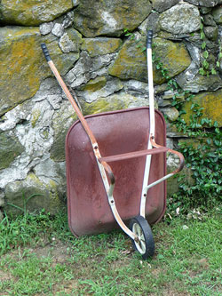 Image of a red wheelbarrow leaning against a stone wall