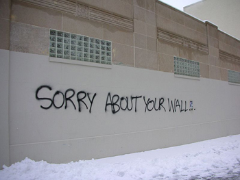 """This photo displays an example of paradox: graffiti on a wall that reads """"Sorry about your wall."""""""