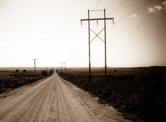 A wide dirt road stretches through the countryside