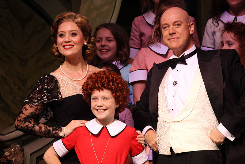 Scene from the musical Annie with Annie and Daddy Warbucks and cast
