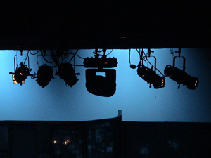 A photograph of stage lights silhouetted against a dimly lit screen