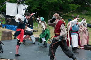A photograph of a sword fight during a play. The fighters are dressed as pirates.