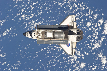 A photograph of the space shuttle Discovery taken in space flight from above; The shuttle's cargo bay doors are open.