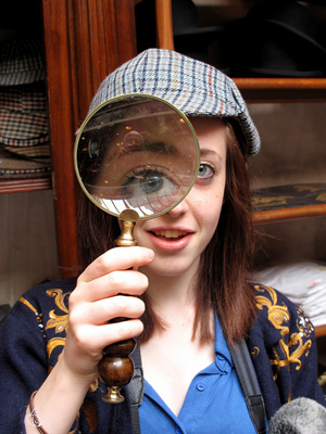 A photograph of a young woman looking through a magnifying glass. She is also wearing a 'Sherlock Holmes' hat