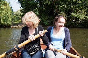 A photograph of two young women rowing a boat on the water