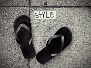 A photograph of a pair of flip flops on a sidewalk with the word 'style' between them