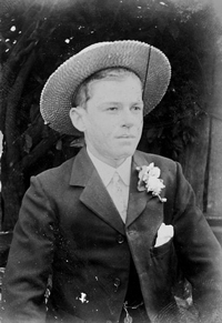 A late 19th century photograph of a young man wearing a suit with a flower in his lapel. He is also wearing a boater hat.