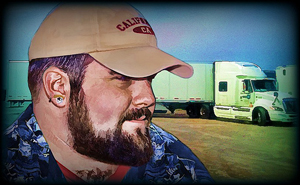 A photograph of a truck driver with his rig in the background. He is wearing a baseball hat.