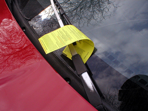 A photograph of a parking ticket on a car's windshield. It has been stuck under one of the wiper blades.
