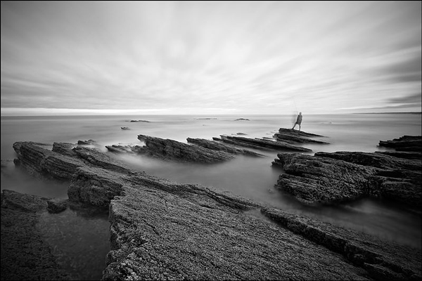 A monochrome photograph of a person standing on rocks at low tide