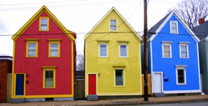 A photograph of three identically built houses that are painted different primary colors