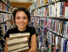 woman standing between shelves in a library