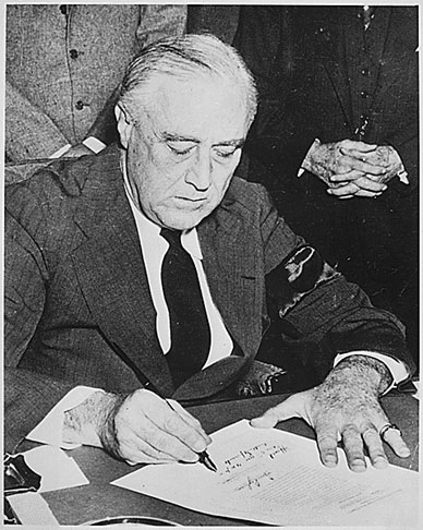 Image of Franklin Delano Roosevelt signing the declaration of war