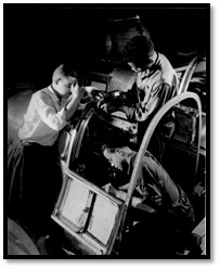Image of three African-American men assembling the cockpit of an airplane
