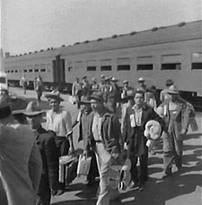 Several men walking off a train, carrying luggage