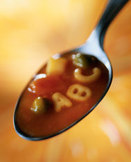A spoon with some soup on it, a red broth, a couple vegetables and 'A, B,C' noodles