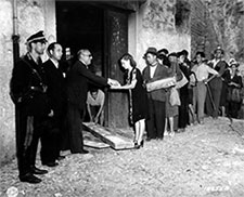 a woman receives bread after waiting in a bread line in Agata, Sicily