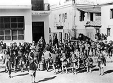 Image of dozens of children waiting in line for lunches in front of a school