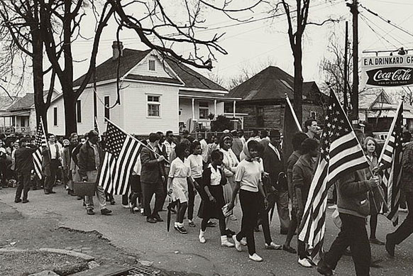 Image of dozens of men and women walking along a street, some are carrying American flags.