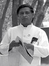 a photograph of Mexican American civil rights leader, Cesar Chavez, holding a newspaper.