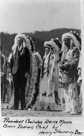 Image of Calvin Coolidge in Sioux Indian headdress, surrounded by a Sioux Indian Chief and woman.