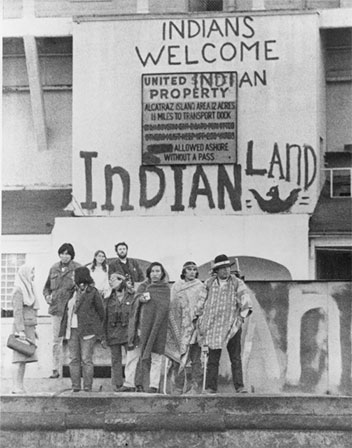Image of several men and women standing outside Alcatraz with a sign in the background welcoming all Indians