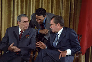 Image of Nixon and Brezhnev seated and one man is leaning down behind them.