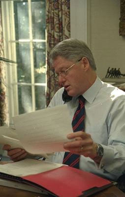 Image of President Clinton talking on the phone while holding papers in his hands.