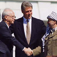 Image of Yitzhak Rabin and Yasser Arafat shaking hands with Bill Clinton in the Background