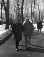 Image of Sadat and Carter walking along a trail at Camp David, both are dressed in overcoats