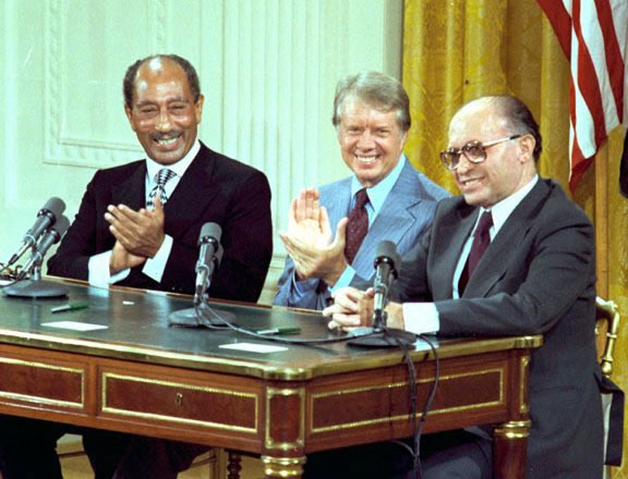 Image of Sadat, Carter, and Begin seated at a desk behind microphones