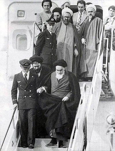 Image of Khomeini exiting an airplane, led by a pilot and surrounded by his followers
