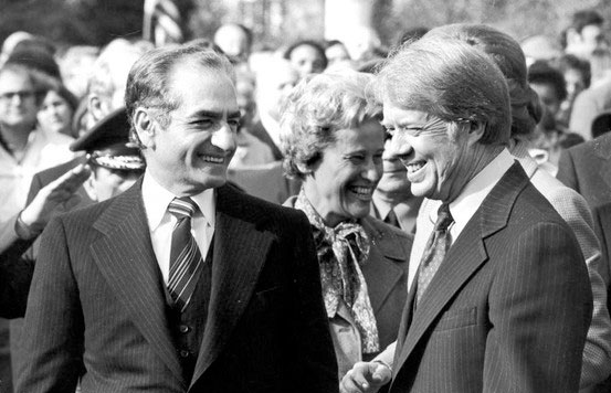 Image of the Shah and Carter standing side by side laughing