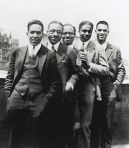 Image of five men standing in a line. Langston Hughes is in the front.