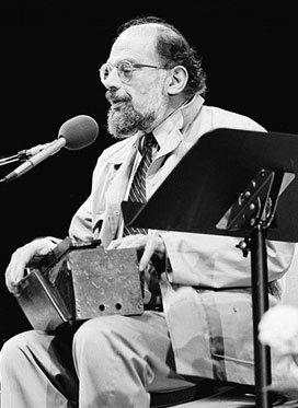 Image of Allen Ginsberg seated holding a box on his lap
