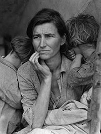 Image of a woman holding a baby, she is flanked by two other small children who have their heads turned away from the camera