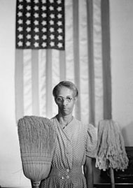 : Image of an African-American woman holding a broom in one hand, and a mop in the other. An American flag is hanging on the wall in the background