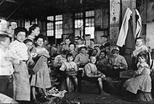 Very young children, mostly under ten years old, stringing beans in a factory near Baltimore, MD.